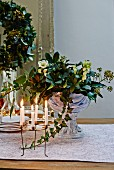 Festive arrangement of hellebores in glass goblet dish and wreath-shaped candelabra on dresser