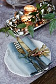 Festive place setting with name tag on floral tablecloth and tendril of foliage plant in foreground