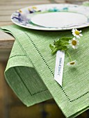 Name tag with chamomile flowers attached to green linen napkin