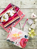 Colourful towels, eye mask with butterfly pattern, soaps and toothbrushes arranged on vintage wooden surface