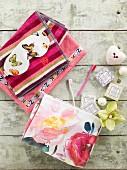 Bunte Handtücher, Augenmaske mit Schmetterlingsmotiv, Seifen und Zahnbürsten auf Vintage Holz arrangiert