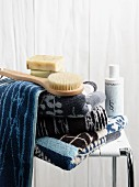 Towels in shades of blue, soaps and body brushes on spa stool
