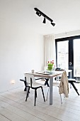 Dining area below black spotlights on lighting rail in minimalist interior with white-painted wooden floor