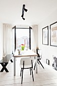 Various black and white chairs and bench around modern dining table in front of open, double balcony doors with view of city