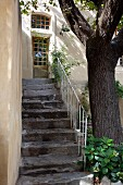 Weathered, stone exterior stairs with white metal balustrade in courtyard