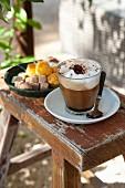 Cappuccino im Glas und Konfekt in Schale auf rustikalem Holzschemel
