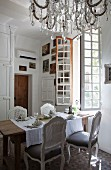 Rococo chairs around set table below open window and chandelier with glass pendants