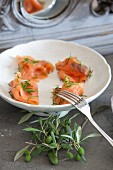 Salmon with dill in white bowl next to olive sprig