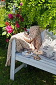 Pastries on cake stand and plate next to crocheted blanket on white wooden bench in garden