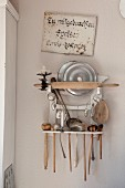 Vintage kitchen utensils on rack on wall painted pastel pink