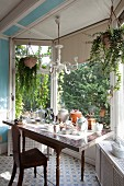 Crockery on table and antique wooden chair in window bay with view of garden