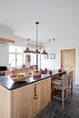 Kücheninsel in einer ländlichen Küche mit Holzverkleidung und Arbeitsplatte aus Stein
