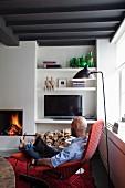 Mann und Hund in gemütlichem rotem Sessel mit Fussschemel, Retro Stehleuchte in Wohnzimmerecke mit Kaminfeuer