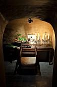 Gewölbekeller mit Kristall-Kerzenleuchtern, Buddhafigur und Gemüseschale auf angestrahltem Holztisch