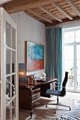 Blick auf Retro-Schreibtisch und Klassiker Bürostuhl in Wohnraumecke mit rustikaler Holzdecke