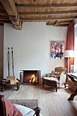 Antiker, gemütlicher Sessel neben Kaminfeuer in rustikalem Raum mit Dielenboden und Holzdecke