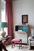 Antiker Polsterschemel vor Vintage-Sekretär und bodenlangem Vorhang