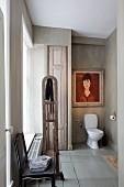 Antiker Stuhl in Vintage-Bad mit weißem WC in hellgrau gestrichener Wandnische und Frauenbildnis in Rottönen