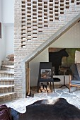Animal-skin rug on stone floor below winding staircase with perforated brick side wall