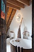 Blick durch offene Tür auf Vintage Badezuber in rustikalem Dachraum mit Holzbalkendecke