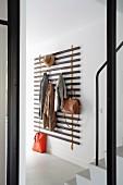 Minimalistische Wandgarderobe aus Holzleisten mit aufgehängter Kleidung in modernem Hauseingang