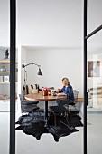 Blick durch offene Glastür auf Frau an rundem Tisch, moderne, schwarze Stühle aus Metallgittern auf Tierfellteppich