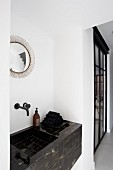 Washstand covered in black marbled tiles below round mirror in bathroom