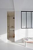 Schmaler Durchgang ins Bad, seitlich weisse Wand mit Innenfenster