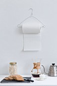 Wore coat hanger used as kitchen roll dispenser