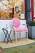 An upholstered Louis XVI-style chair with a pink-and-white striped jersey cover