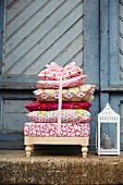 A stack of cushions on a foot stool next to a lantern