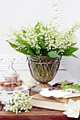 Bouquet of lily-of-the-valley in vintage metal and glass vase on table