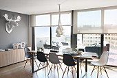Dining set with Eames Chairs next to glass wall in penthouse apartment; stylised hunting trophy on wall