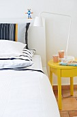 Striped pillows on white bed next to sunshine yellow bedside table