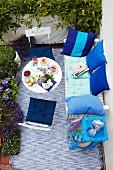 Sommerlicher Balkon mit gedecktem Tisch von oben gesehen; Kissen in Aquatönen auf weissen Outdoor-Möbeln