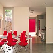 Esstisch und rote, gepolsterte Designerstühle auf Estrichboden, Blick durch raumhohen Durchgang in Küche mit Barhockern vor Theke
