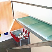 Staircase with walkway landing made from glass panels, view into open-plan dining area with table and red chairs