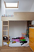 Child's attic bedroom - custom loft bed with ladder under skylight, futon sofa and chest of drawers with yellow front