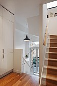 Stairwell with white wooden treads, runner and white fitted cupboard on landing
