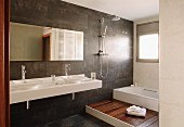 View into designer bathroom - white washstand with twin basins against dark-tiled wall and wooden platform leading to bathtub