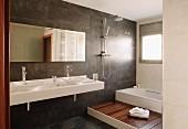 Blick ins Designerbad, weisser Waschtisch mit zwei Schüsseln vor dunkel gefliester Wand, seitlich Podest mit Holzboden vor Badewanne