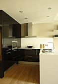 White kitchen counter and fitted cupboards with glossy, black fronts in open-plan kitchen