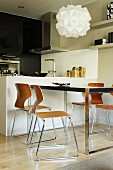 Designer pendant lamp above table and retro shell chairs next to monolithic white counter in open-plan kitchen