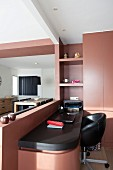 Narrow desk and black swivel chair next to custom fitted cupboards with red-brown fronts; dining area in background