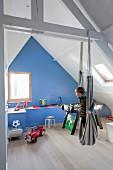 Kind in Hängematte im Kinderzimmer unter dem Dach, mit sichtbarer Holzkonstruktion, im Hintergrund blau getönte Giebelwand