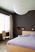 Double bed with lilac bed linen in bedroom painted dark brown