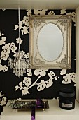Antique mirror and miniature chandelier above shelf in cloakroom with floral black and white wallpaper