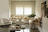 Sofa combination with beige upholster on platforms in window niche with roller blinds; retro easy chair and collection of various items on polished concrete floor