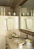 Antique mirror with silver frame above washstand with oval undermount sink decorated with soaps in silver boxes and candles