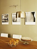 Muffins and cake on dining table; pendant lamps with metal lampshades and artistic black and white photos on wall